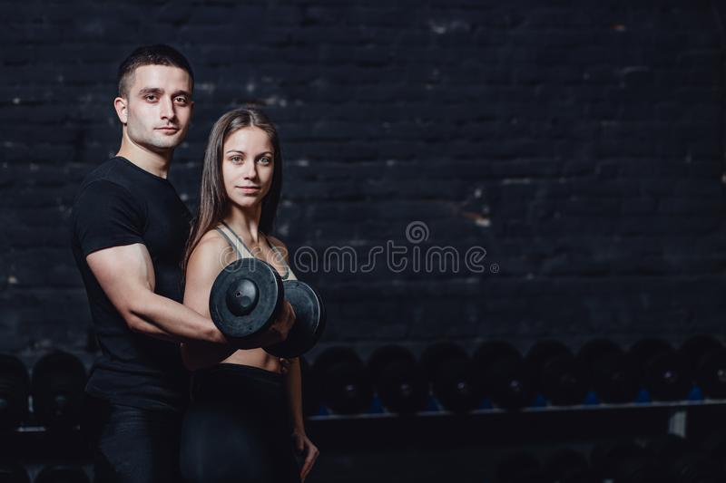 Two young guys and girls are engaged in the gym. During this time, they embraced themselves holding their weights in. Their hands. On a black background stock photo