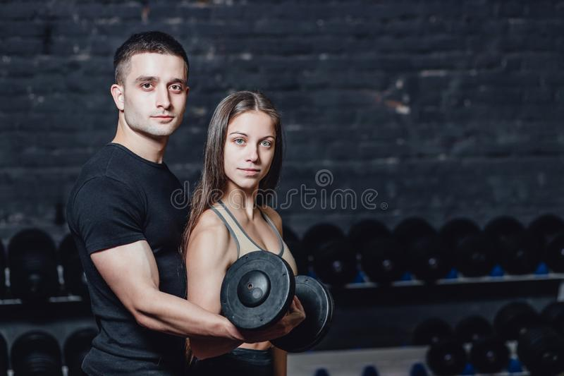 Two young guys and girls are engaged in the gym. During this time, they embraced themselves holding their weights in. Their hands. On a black background royalty free stock photo