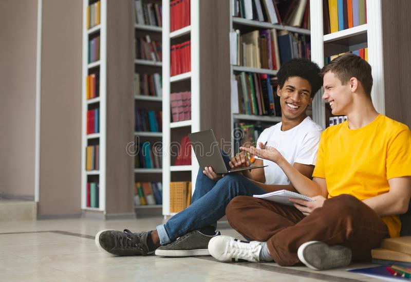 Two young guys having fun while studying at library. Two multiracial guys having fun while studying at library, using laptop, sitting on floor, free space stock images