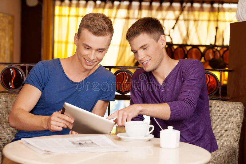 Two young guys talking in cafe. royalty free stock image