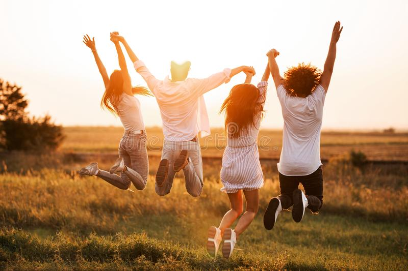 Two young guys and two girls are holding their hand and jumping in the field on a summer day. Back view. stock photos