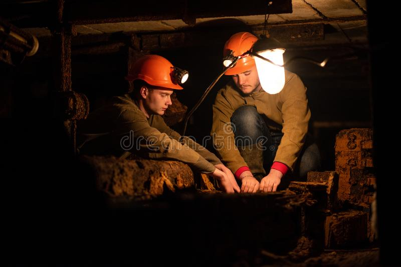 Two young guys in a working uniform and protective helmets, sitting in a low tunnel. Workers of the mine stock photos
