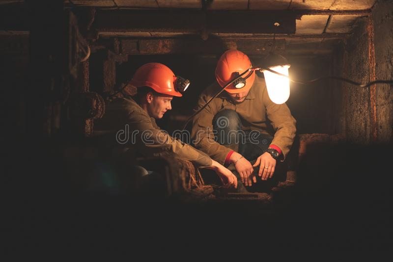 Two young guys in a working uniform and protective helmets. Sitting in a low tunnel. Workers of the mine. Miners stock image