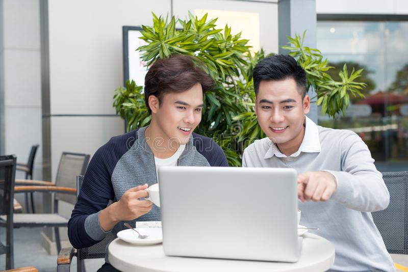 Two young handsome businessmen in casual clothes smiling, talking in coffee shop. Two young handsome businessmen in casual clothes smiling, talking in coffee stock images