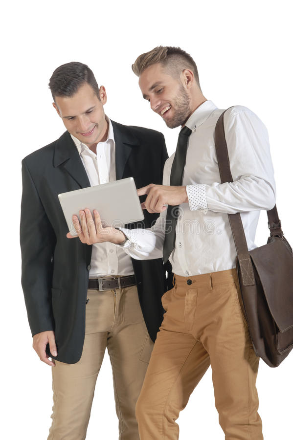 Two young handsome businessmen working with digital tablet. Isolated on white background stock photography