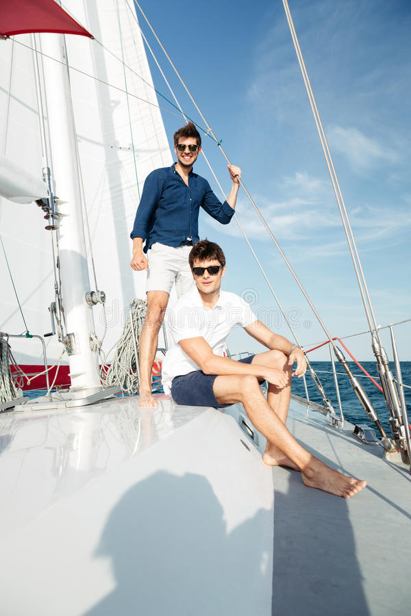 Two young handsome happy men standing on the yacht. Two young handsome happy men friends standing on the yacht royalty free stock image