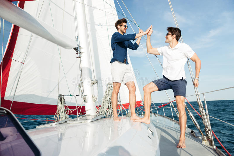 Two young handsome men greeting standing on the yacht. Two young handsome men greeting each other while standing on the yacht royalty free stock photo