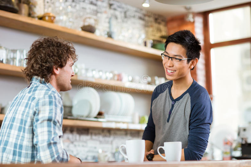 Two young handsome men talking in cafe. Two young handsome men drinking tea and talking in cafe royalty free stock images