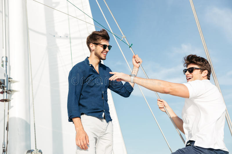 Two young handsome men talking while standing on the yacht. Two young handsome happy men talking while standing on the yacht royalty free stock photos