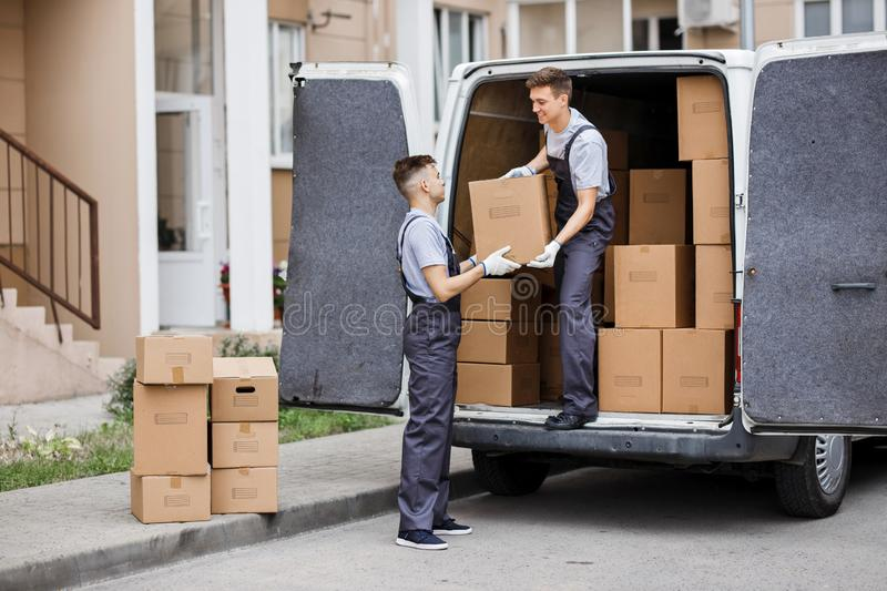 Two young handsome movers wearing uniforms are unloading the van full of boxes. House move, mover service.  stock image