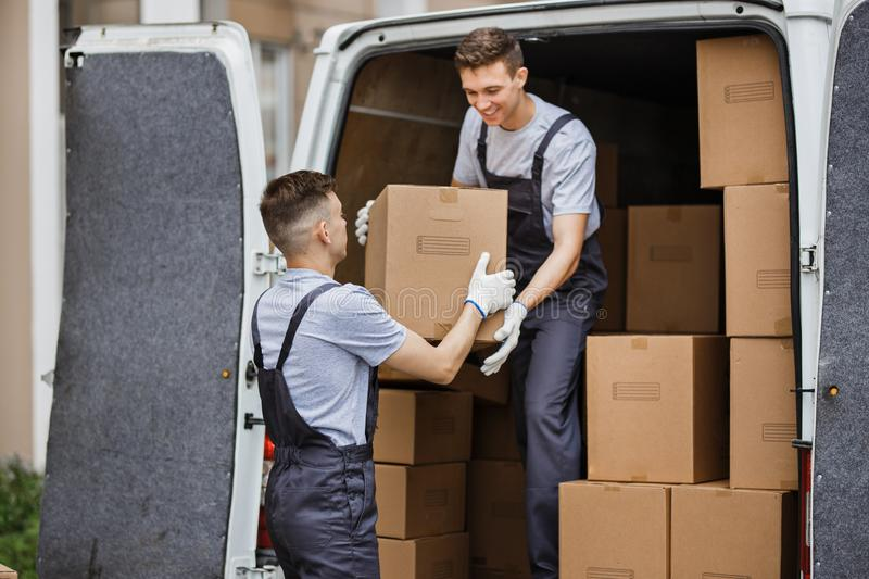 Two young handsome movers wearing uniforms are unloading the van full of boxes. House move, mover service royalty free stock photos