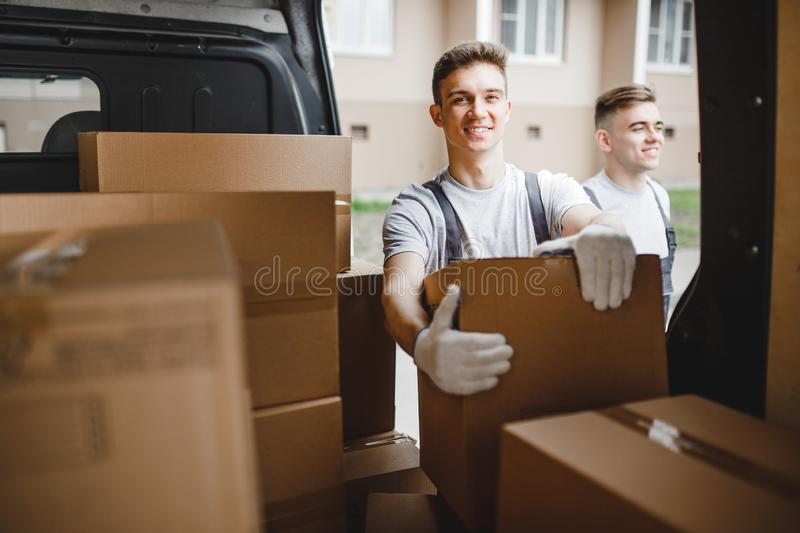 Two young handsome workers wearing uniforms are standing next to the van full of boxes. House move, mover service.  royalty free stock photo