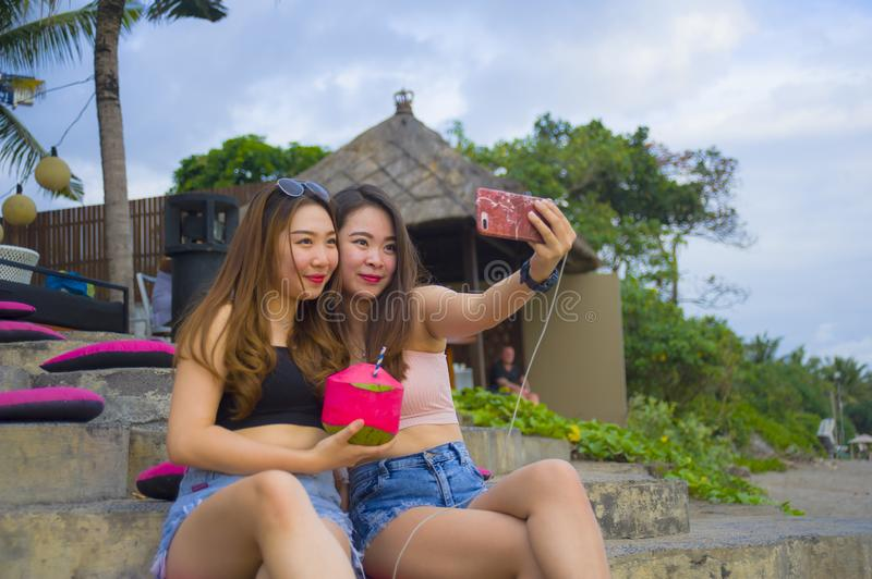 Two young happy and attractive Asian Chinese and Korean women hanging out , girlfriends enjoying holidays trip in tropical resort royalty free stock photography