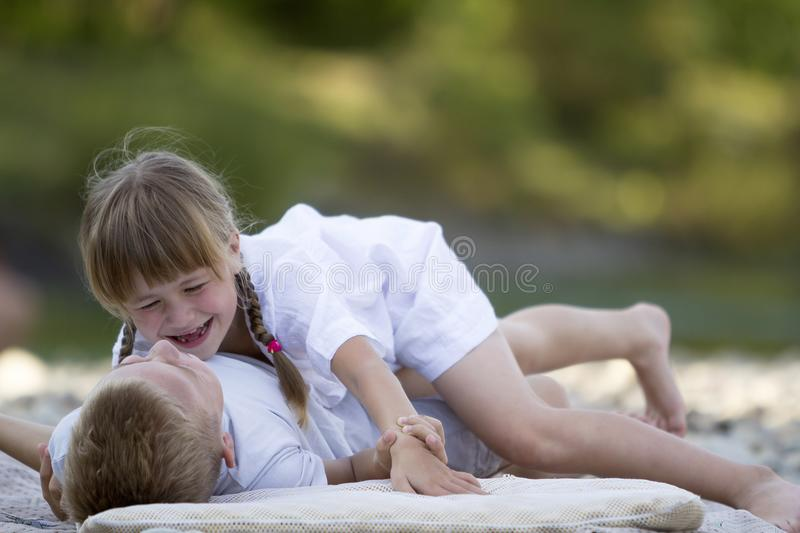 Two young happy cute blond laughing children, boy and girl, brother and sister having fun on pebbled beach on blurred bright stock photos