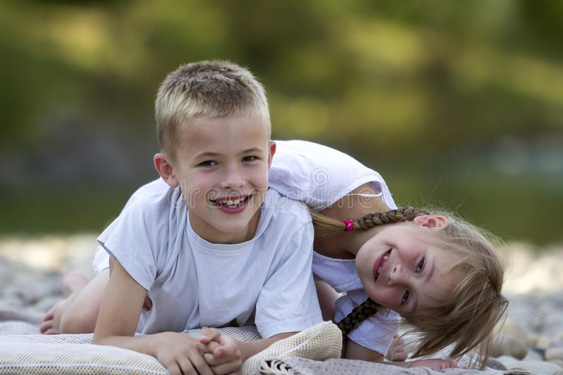 Two young happy cute blond smiling children, boy and girl, broth stock photo