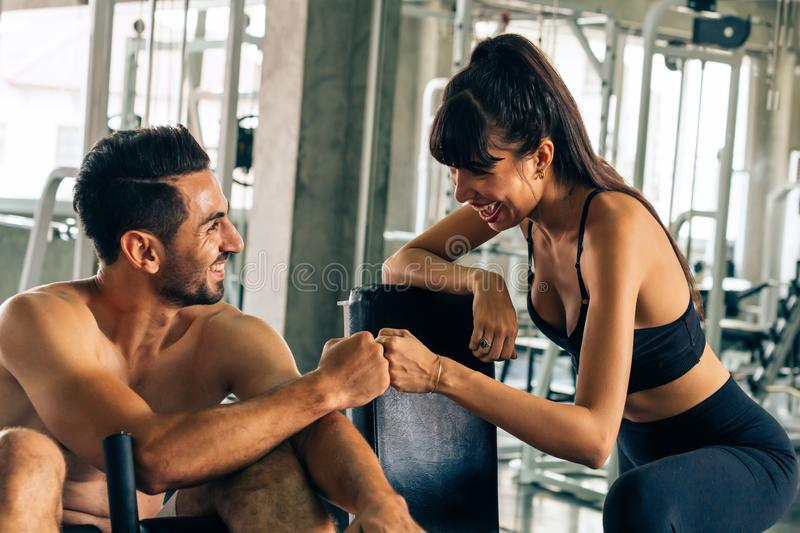 Two young happy fitness buddies doing fist bump in gym stock photography