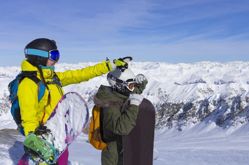 Two young happy friends snowboarders are having fun on ski slope with snowboards in sunny day royalty free stock image