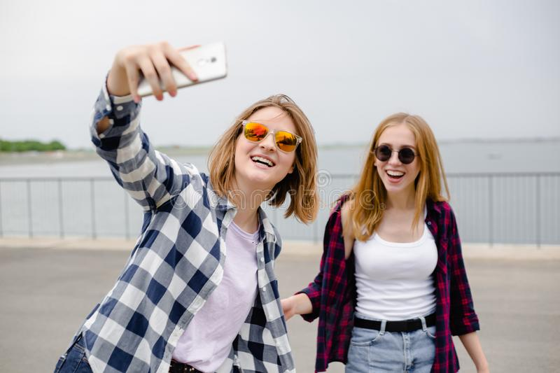 Two young happy girl friends in hipster making selfie on phone.  royalty free stock photos