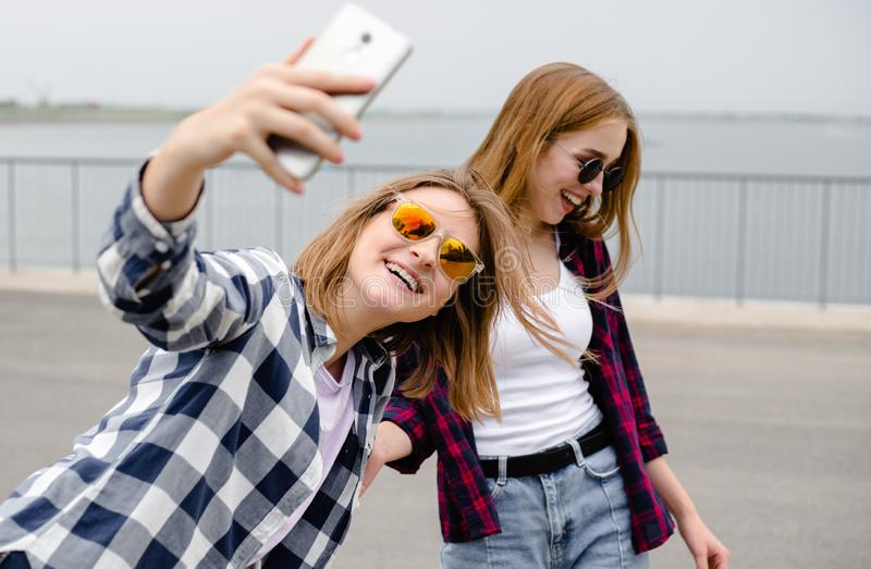 Two young happy girl friends in hipster making selfie on phone.  royalty free stock photography