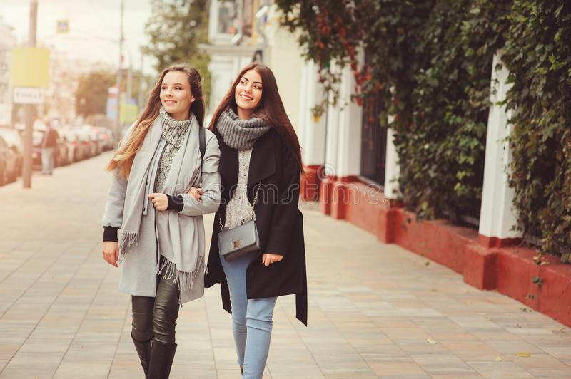 Two young happy girlfriends walking on city streets in casual fashion outfits royalty free stock images