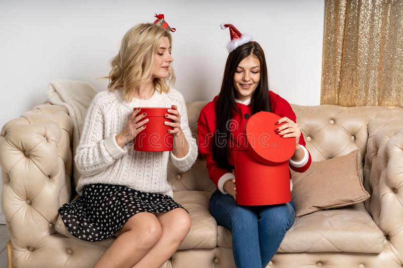 Two young happy girls in stylish sweaters and santa hats stock photo