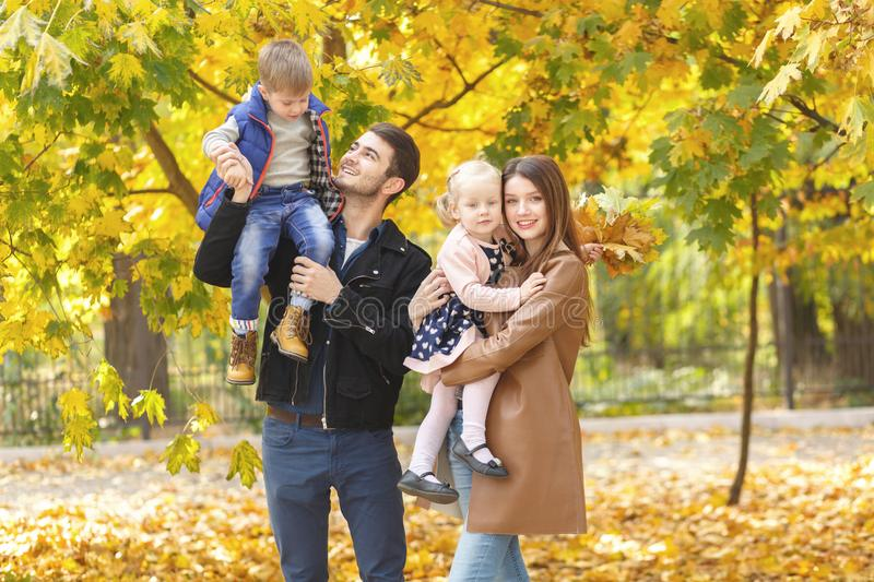 Two happy parents hold their young children in their arms. In the autumn park. royalty free stock images