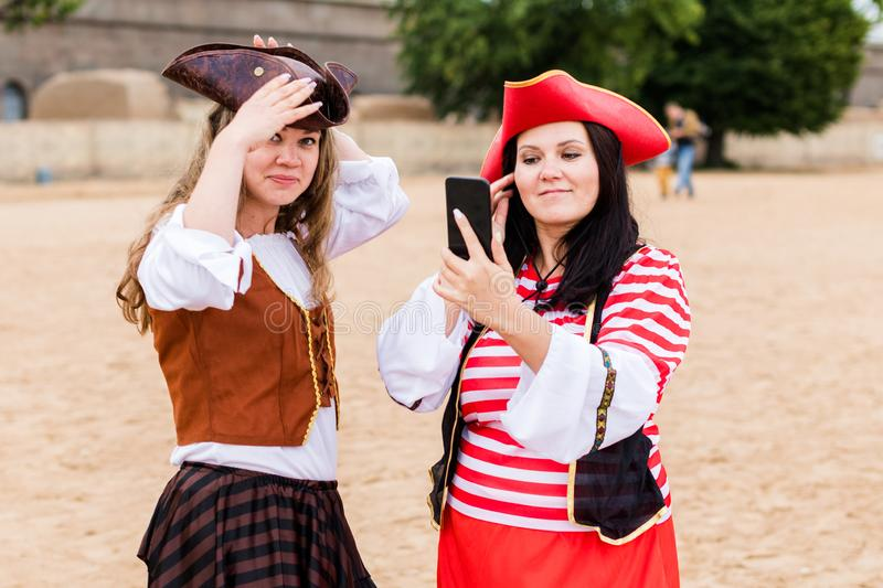 Two young happy smiling Caucasian women in pirate costumes preen with smartphone. Backstage. Two young happy smiling Caucasian women in pirate costumes preen stock images