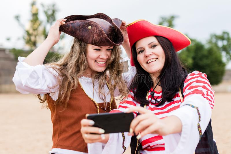 Two young happy smiling Caucasian women in pirate costumes taking selfie on smartphone. Two young happy smiling Caucasian women in pirate costumes taking a stock image