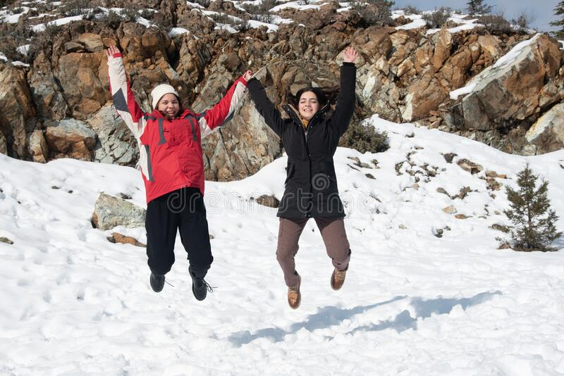 Two young happy teenage girls jumping with pleasure at snow stock photography