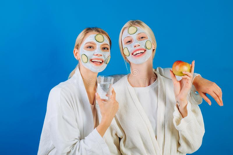Two young happy women with facial mask and cucumber slices at face go healthy lifestyle. Girls holding glass of water royalty free stock images