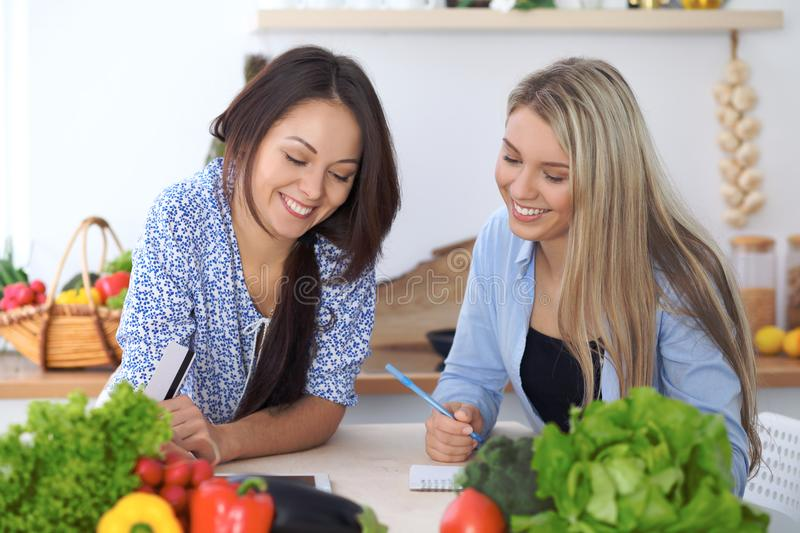 Two young happy women making online shopping for making menu by tablet computer. Friends cooking in the kitchen stock image