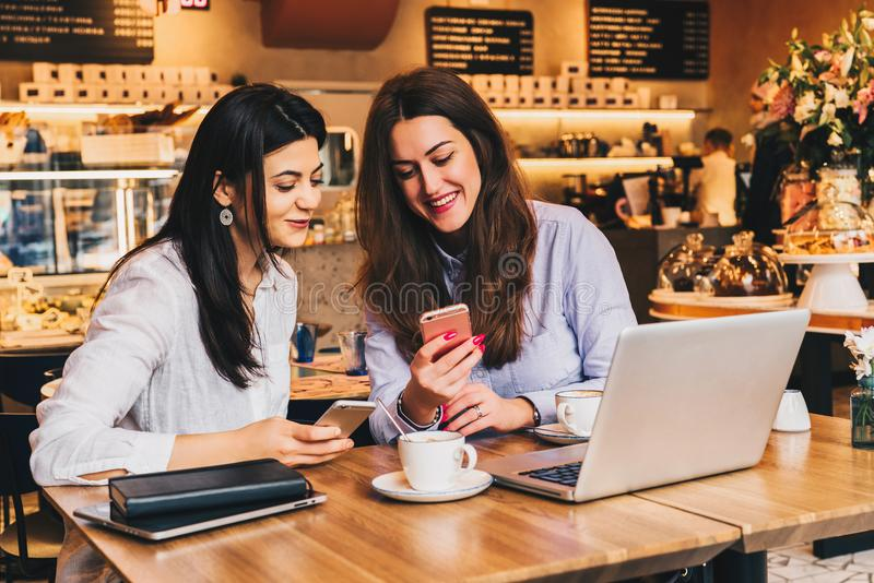 Two young happy women are sitting in cafe at table in front of laptop, using smartphone and laughing. On table paper notebook and cup of coffee. Girls are royalty free stock image