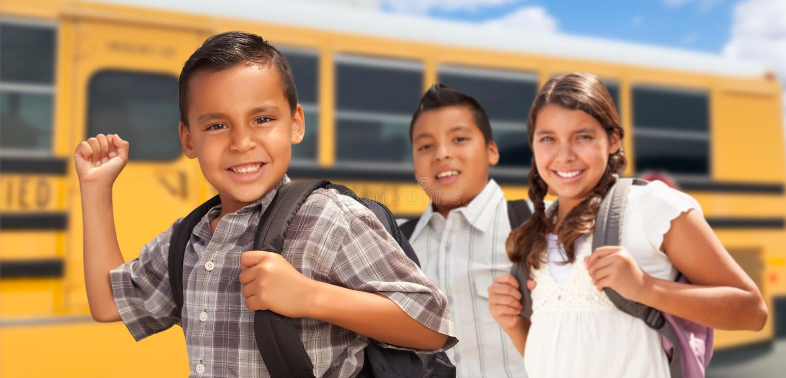 Excited Young Hispanic Boys and Girl Walking Near School Bus royalty free stock photography