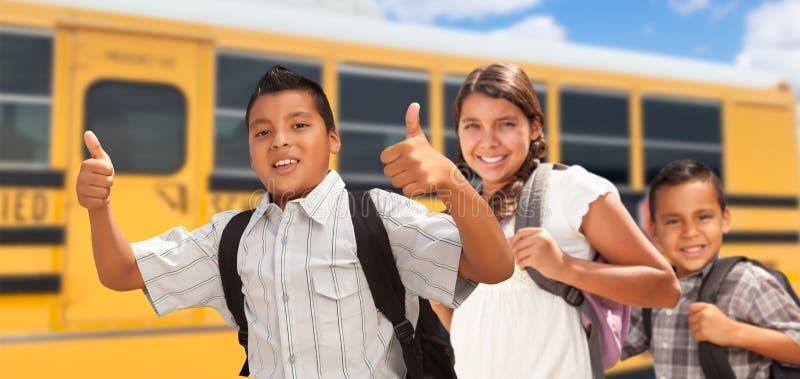 Happy Young Hispanic Boys and Girl Walking Near School Bus royalty free stock photos