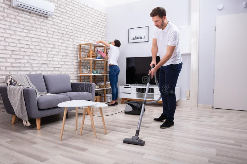 Two Young Janitors Cleaning The Living Room royalty free stock photography