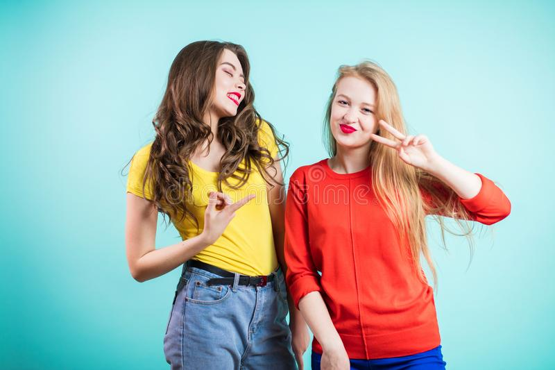 Two young joyful women on blue background. Youth, happiness, fashion, friendshi. stock photography