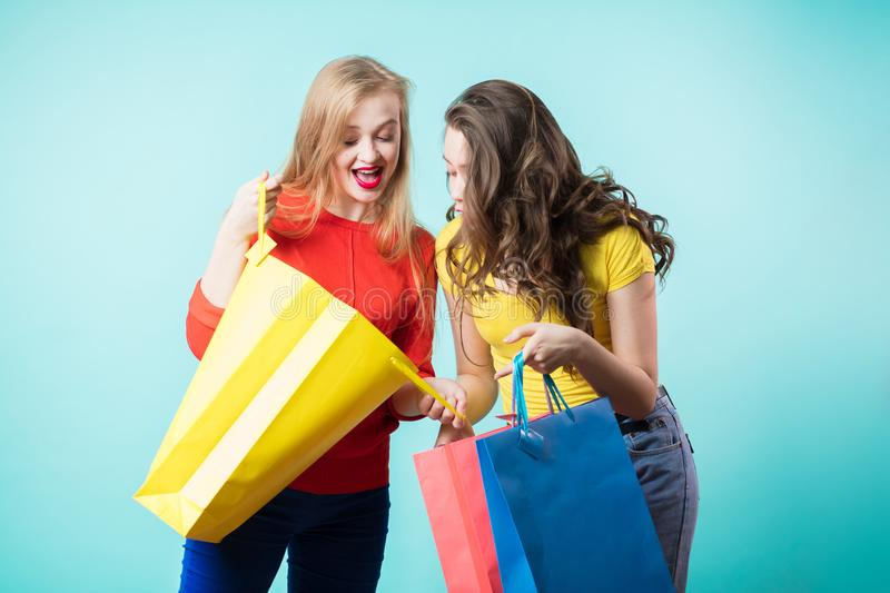 Two young joyful women with colorful shopping bags on blue background. stock photo