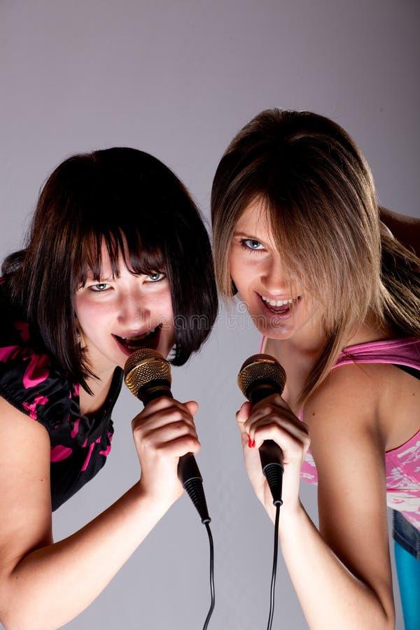 Two young karaoke girls stock photography
