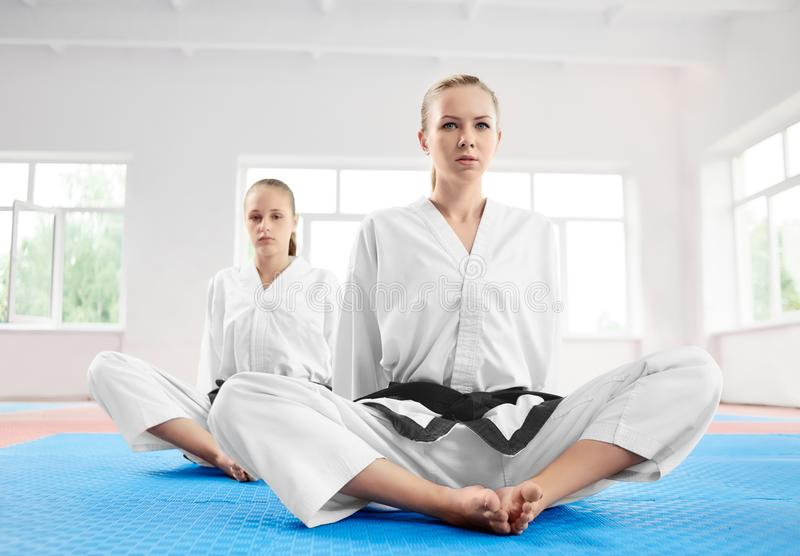 Two young karate girl sittting in lotus position after training in light gym. royalty free stock photos