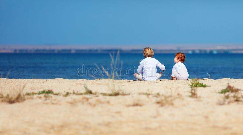 Two young kids, brothers sitting on sandy beach in the morning near the lake stock image