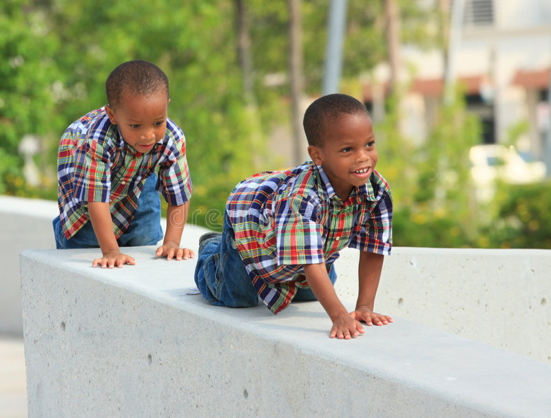 Two Young Kids Crawling On Ledge. Two young twins crawling on a concrete ledge stock images