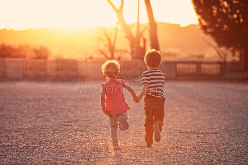 Two young kids runs on the sunny day stock images
