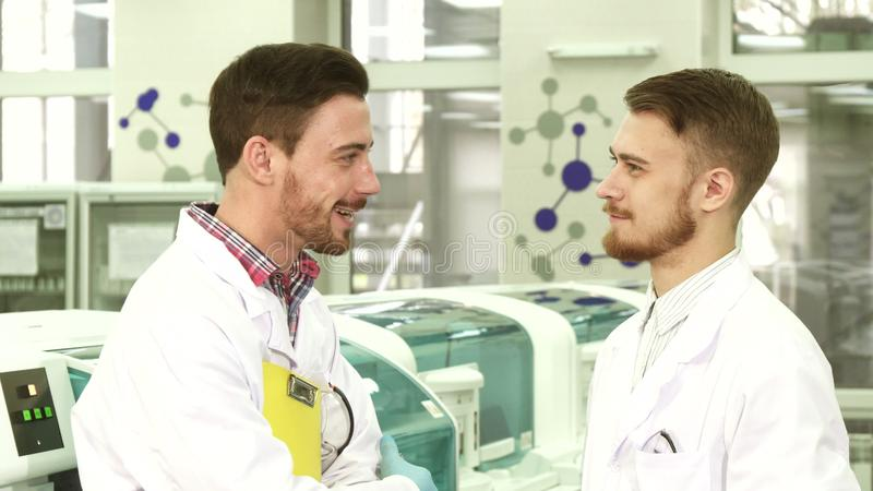 Two young lab technicians stand in the middle of the laboratory and talk stock photography