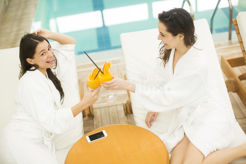 Two young ladies clothed bathrobe lying down. On deckchairs, and having fun in the spa royalty free stock photos