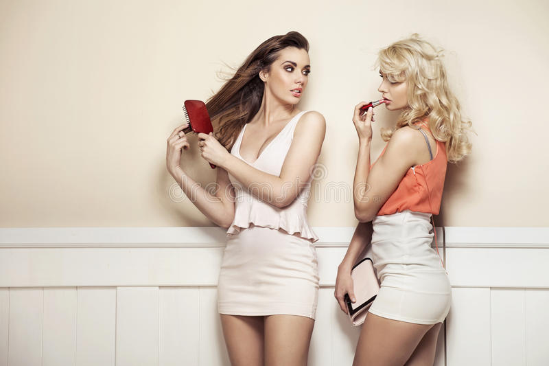 Two Young Beauties Making Preparations To A Party Stock Photography