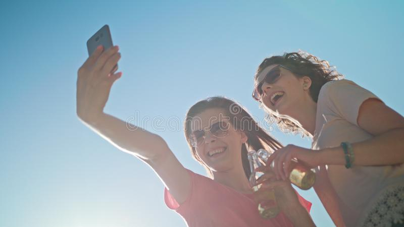 Two Young Ladies Making a Selfie on the Beach stock photos