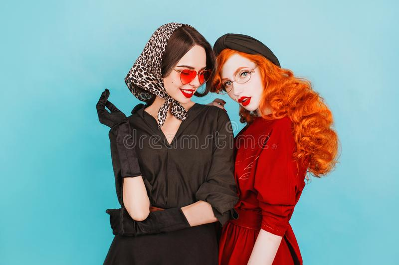 Two young lesbian girls with curly long hair in black retro dress and sunglasses. Beautiful retro woman with pale skin and red royalty free stock images
