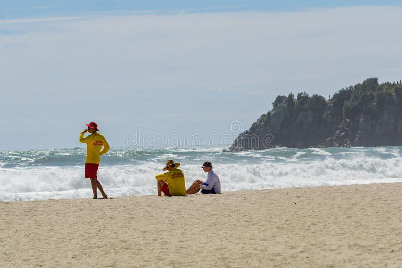 Two young lifeguards and a boy sit on hazy beach watch the rough dangerous surf royalty free stock photography