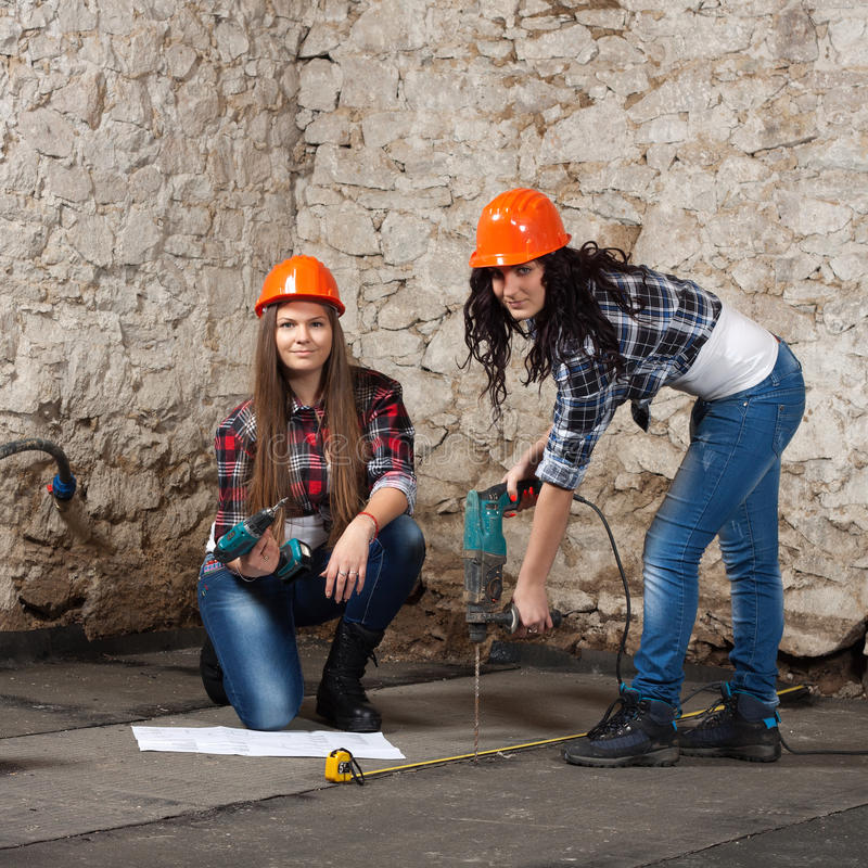 Two young long-haired woman with a drill royalty free stock photo