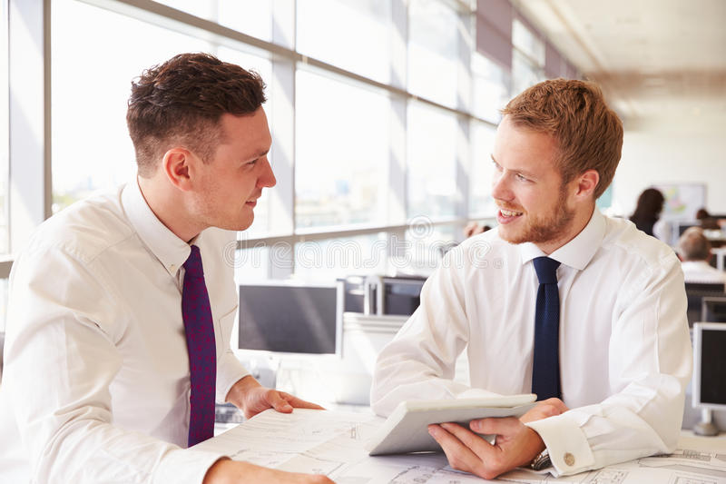 Two young male architects in discussion at an office desk stock photo